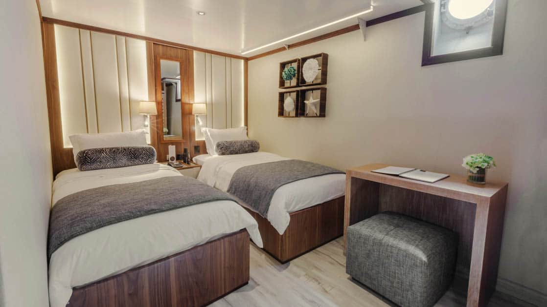 Evolution stateroom with twin beds, desk with ottoman and porthole.