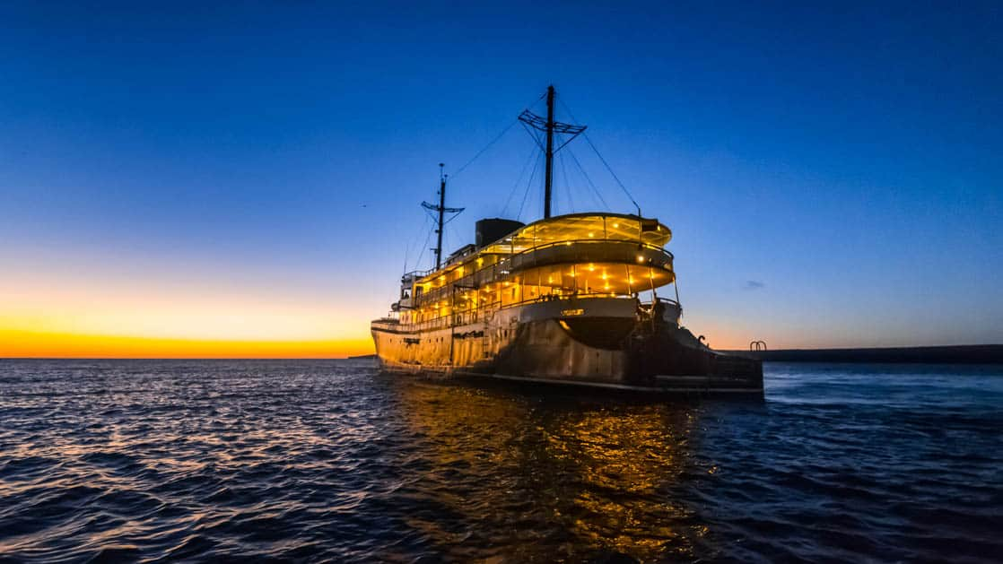 Small ship cruise Evolution at sunset with clear blue skies sailing in the Galapagos.
