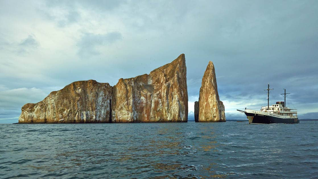 Small ship cruise Evolution next to Kicker Rock in the Galapagos.