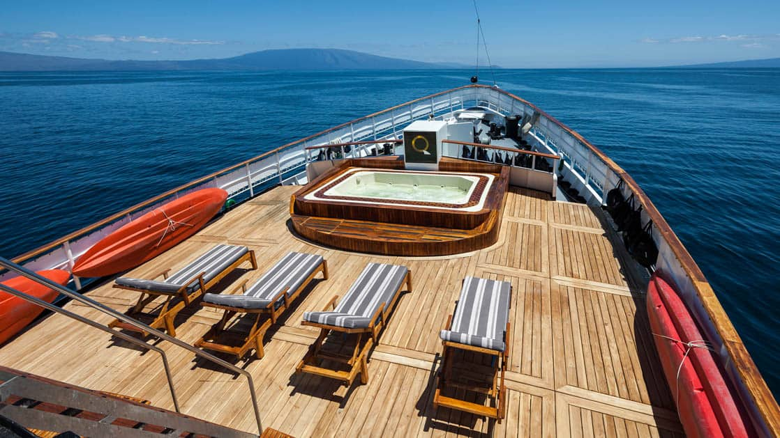 Hot tub, lounge chairs and kayaks off to the side on the bow deck of the small ship Evolution.