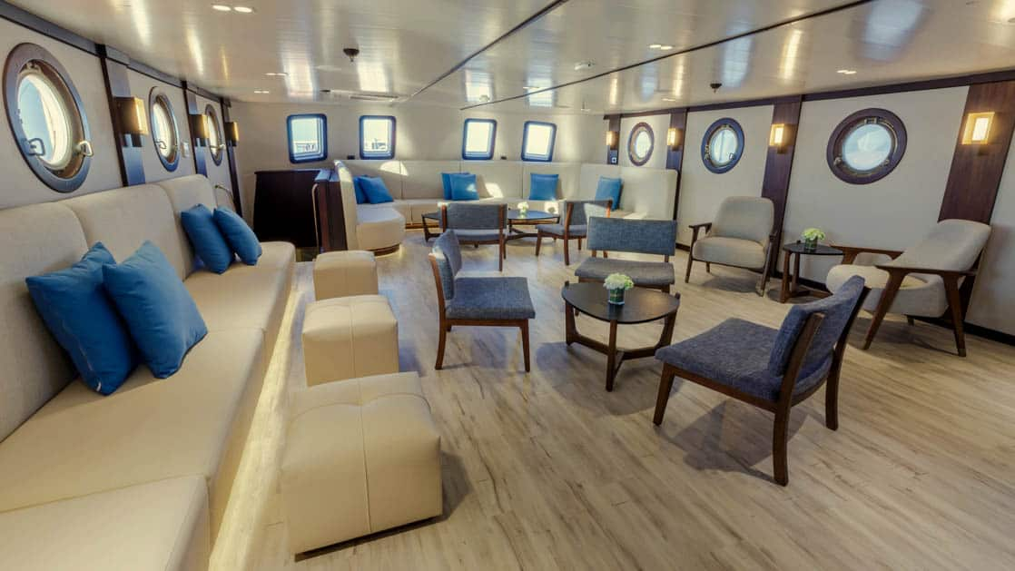 Lounge area on the Evolution with banquette seating, chairs and small tables with portholes.