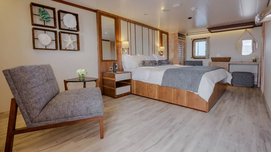 Evolution Master Suite with king bed, seating area, nightstands, reading lights, dresser and desk with windows.