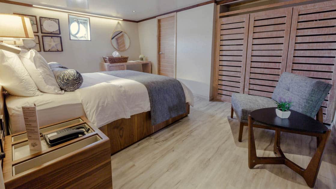 Evolution stateroom with double bed, chair, end table, nightstand and porthole.
