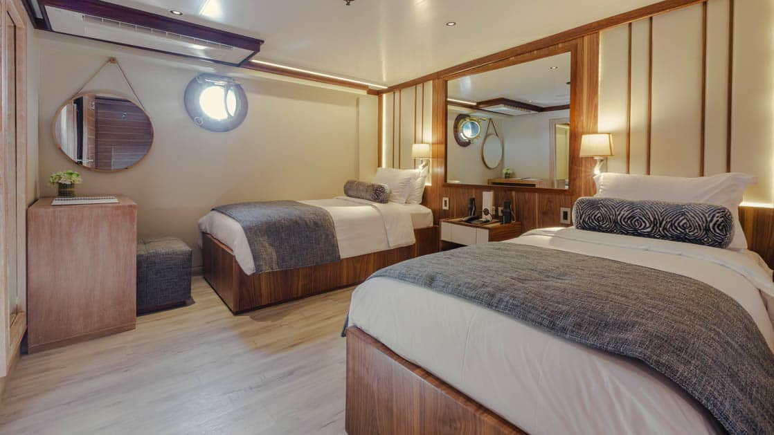 Evolution Premium Stateroom with twin beds, nightstand, desk and porthole.