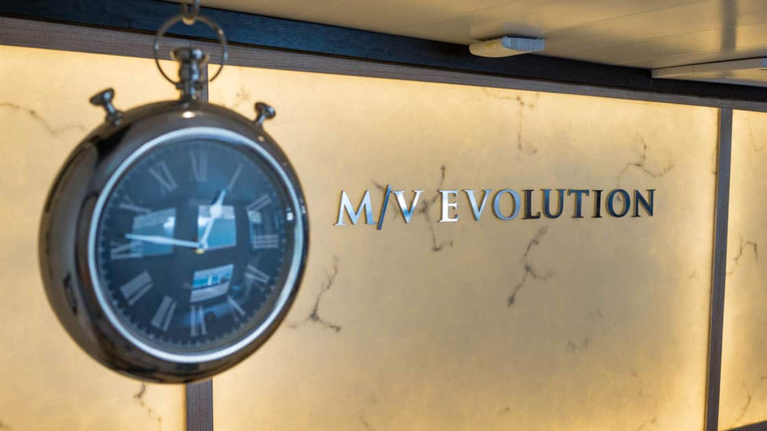 Clock next on a wall with the ship name M/V Evolution