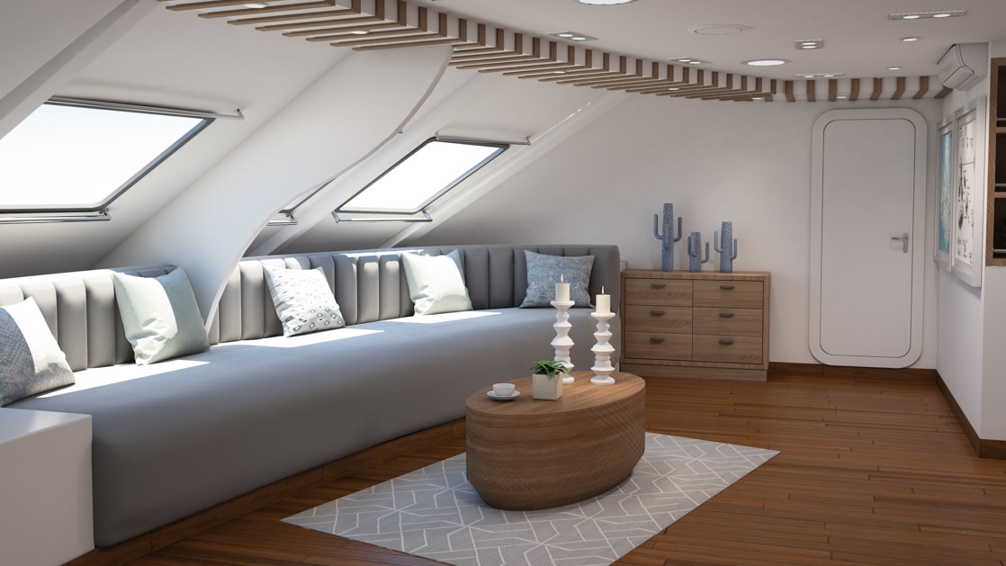 Couch below windows with a table and wood flooring in the Ocean Spray catamaran's lounge area.