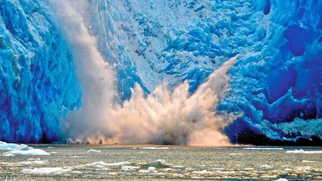 Close up of a calving glacier falling into the water and making waves in ALaska