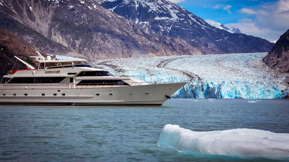 Golden Eagle yacht cruising in front of Glacier in southeast Alaska with icebergs around.