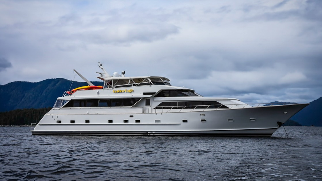Starboard exterior of the white Golden Eagle yacht on a cloudy day in ALaska.
