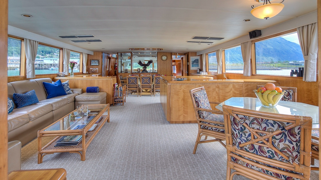 Large tan leather couch and coffee table across from another table in the lounge aboard Golden Eagle.