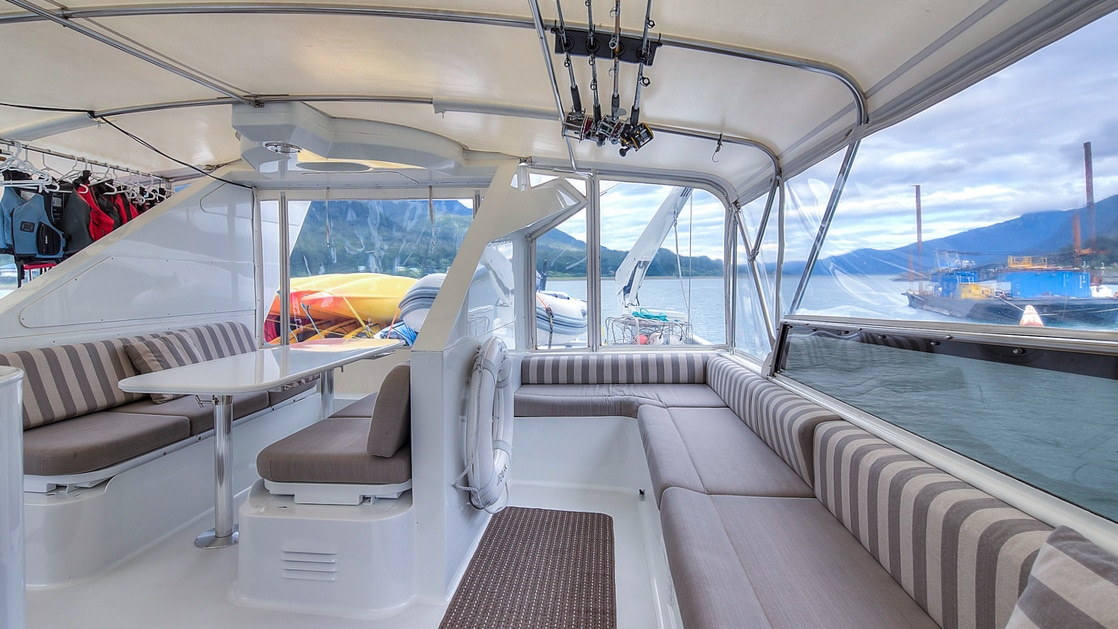 Upper outdoor deck aboard Golden Eagle with covered protection from the wind and rain with wrap around benches for seating.