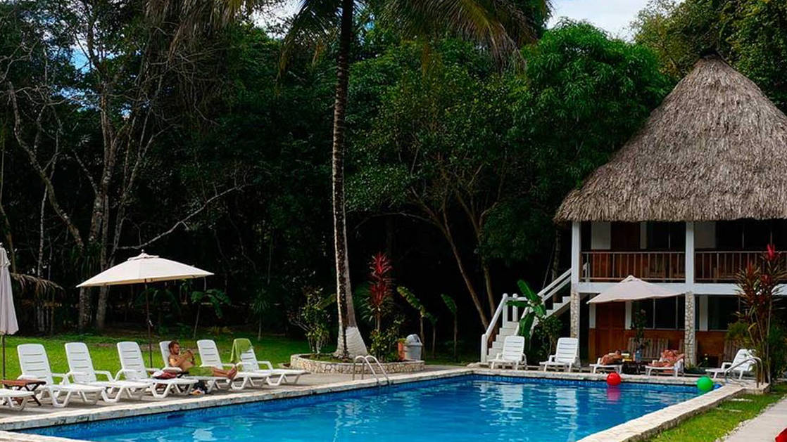 A large pool with lounge chairs and the Tikal Inn a two story building with grass roof.