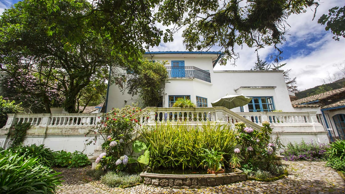 A guesthouse inside Hacienda Cusin, a 17th century estate found in Ecuador's Andes. White walls with bright blue window treatments and roof match the blue clounded sky, framed by lush green garden and foliage.