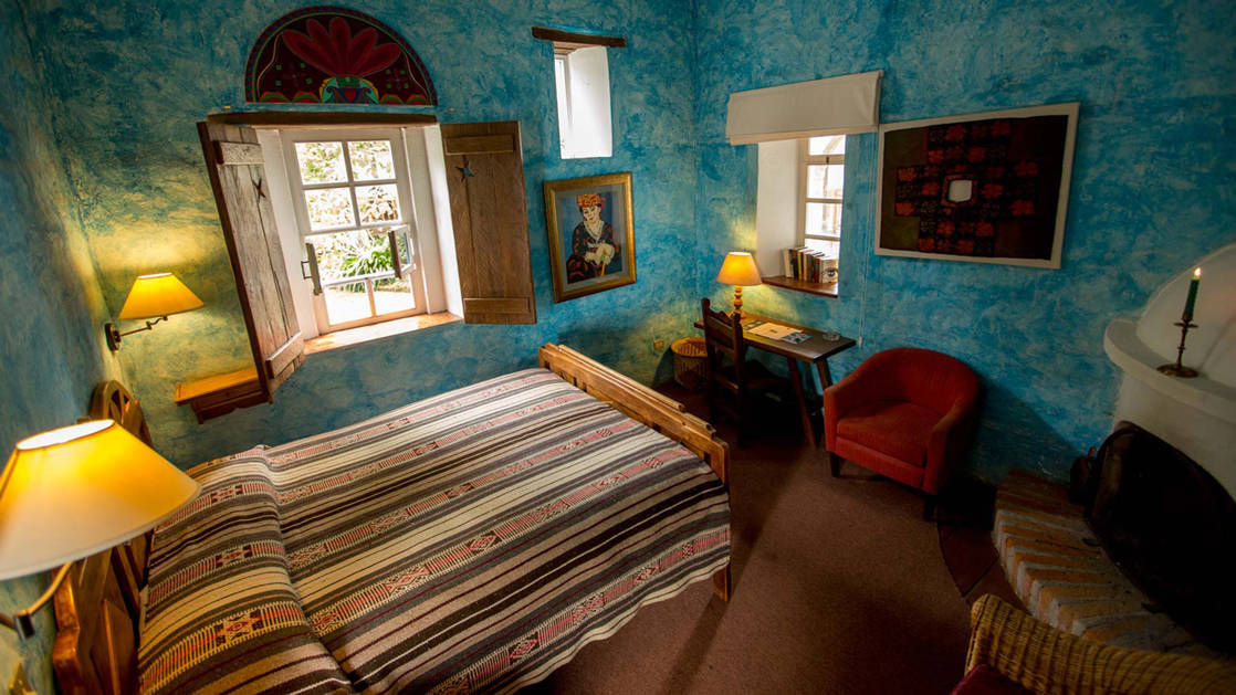 Inside a guestroom at Hacienda Cusin, blue textured walls adorned with Ecuadorian artwork, a fireplace, and a shuttered window to the outsidea stay here as part of an Ecuador land tour,