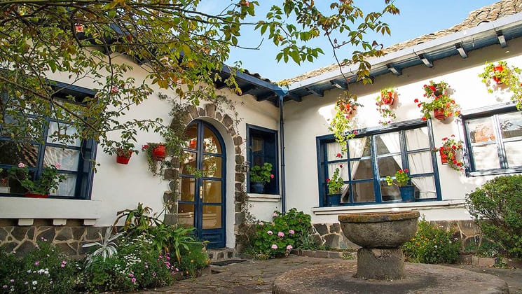 Spotless white walls and blue wooden pained windows of Hacienda Zuleta, seen from a center courtyard with water fountain, from the overhanging roof, brightly colored flowers inside flower pots hang.