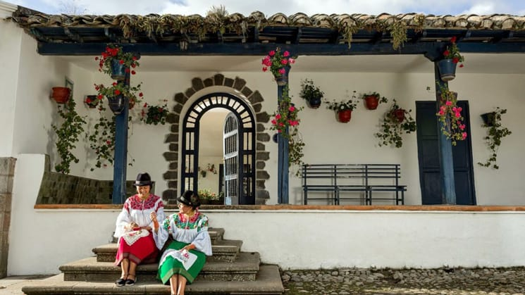 Two Ecuadorian women dressed in green and red traditional clothing woth black hats, sit on the entry steps to Hacienda Zuleta, an estate in Ecuador's highlands. The building has spotless white walls with blue wodden accents and brightly colored potted flowers that hang from the overhanging roof, stay here as part of an Ecuador land tour