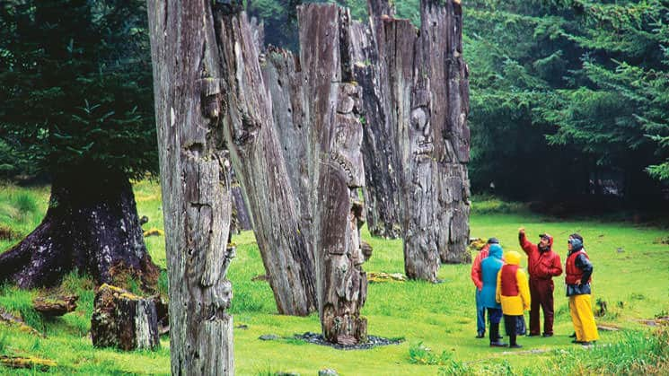 Small ship cruise passengers with their guide in the forest in Haida Gwaii, British Columbia looking at old totems