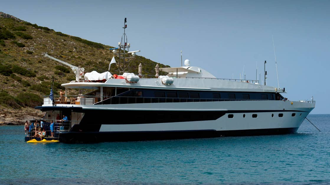 Harmony G yacht anchored off the shoreline in the Mediterranean with a kayak and passengers on the stern swim step.