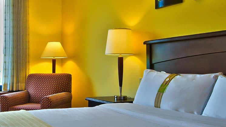 room with king bed at the holiday inn panama canal with lime green walls and two illuminated lamps