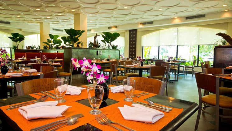 dining room at the holiday inn hotel panama canal with bright orange place mats, flowers on the tables and textured white ceiling