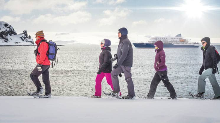 Passengers snowshoeing on the snowy shore in Antarctica with the Hondius in the background.