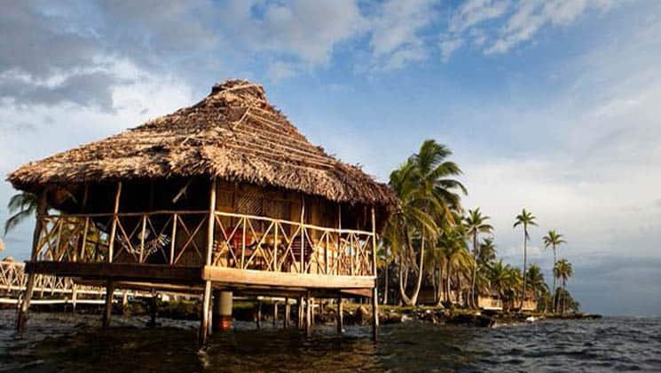 A thatched-roof cabana on a platform above the water and adjacent to a grove of palm trees, the Yandup Lodge in the San Blas islands in Panama is paradise