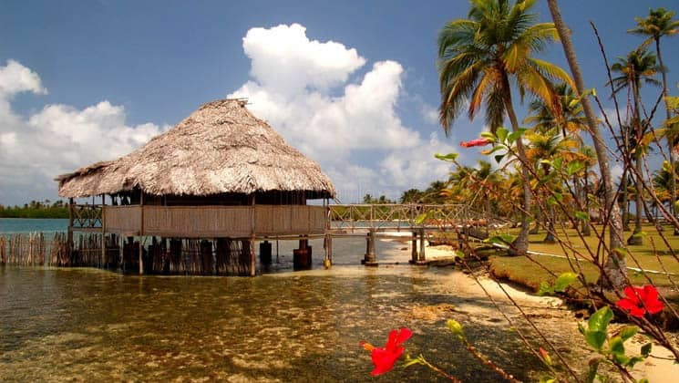 A side view of a cabana with a thatch-roof, built on a platform above the water, is connected to the island. The idyllic eco Hotel Yandup in San Blas, Panama, is a slice of paradise