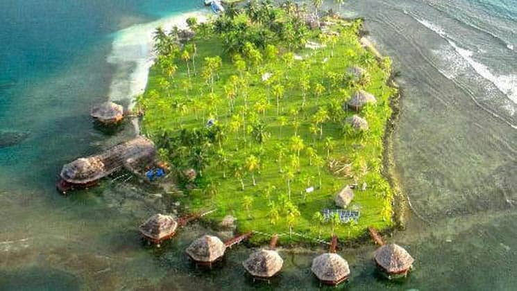 An aerial view of the idyllic eco Hotel Yandup, with thatch-roof cabanas on platforms above the water and adjacent to the island in San Blas, Panama