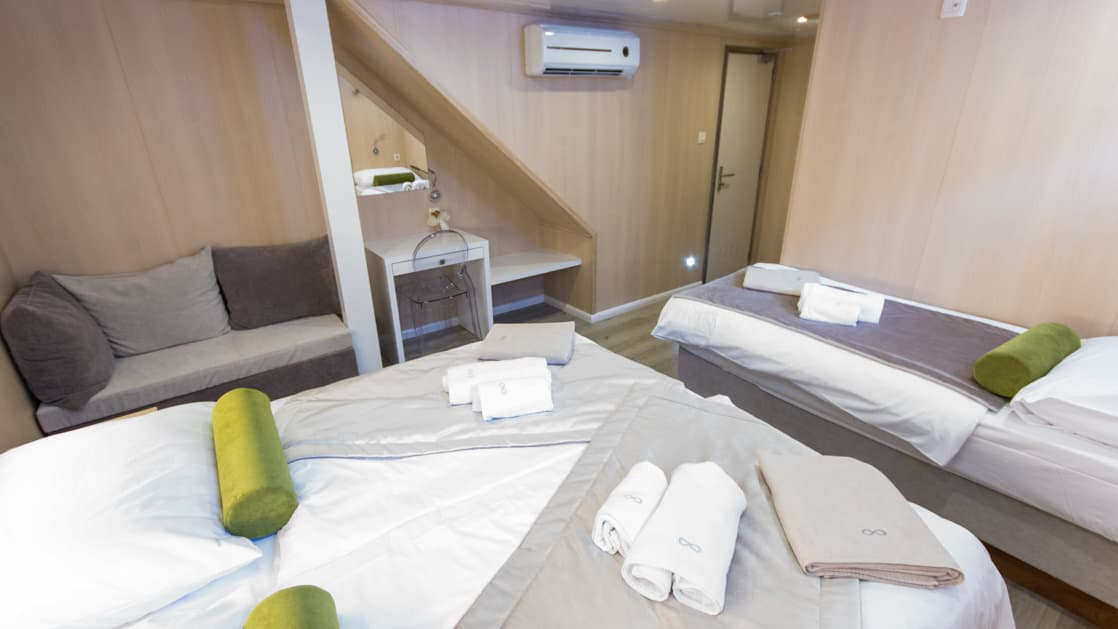 Infinity stateroom with double and twin bed, seating, desk and bathroom.