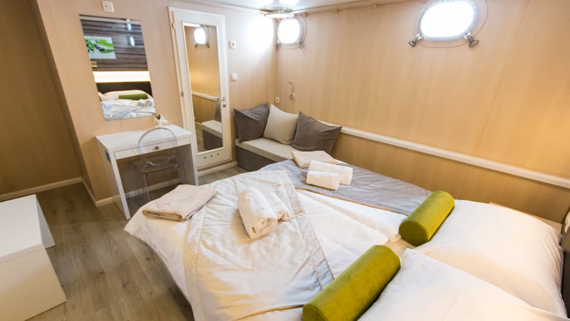 Infinity stateroom with double bed, desk, bathroom, portholes and seating.