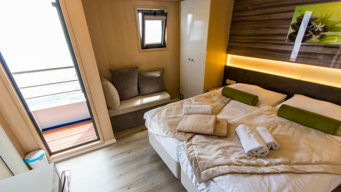 Infinity stateroom with double bed, seating, nightstand and door out to the balcony.