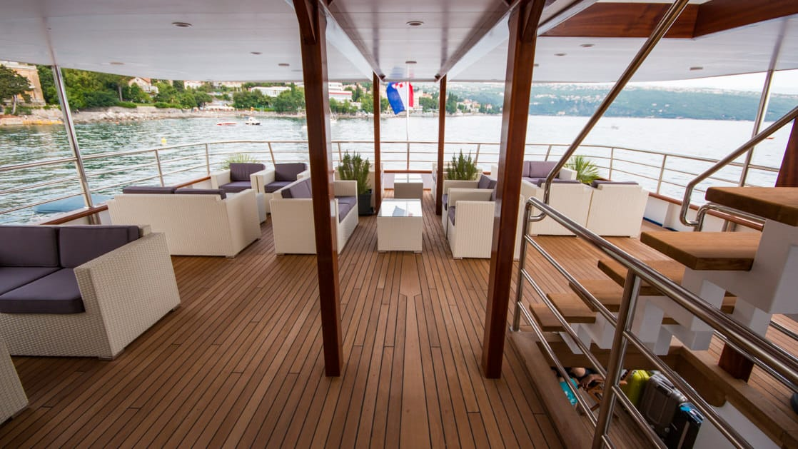 Outdoor sundeck with couches, chairs, coffee tables and stairwell at the stern of the Infinity.
