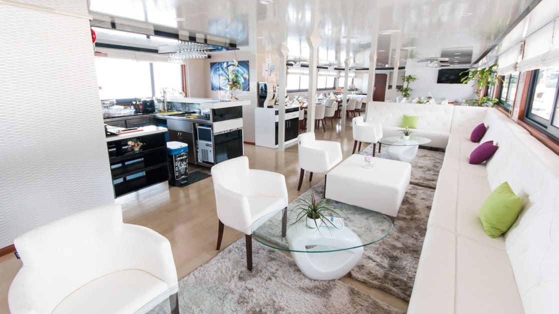 Infinity lounge with couches, chairs, glass coffee tables, ottomans, service station and bar.