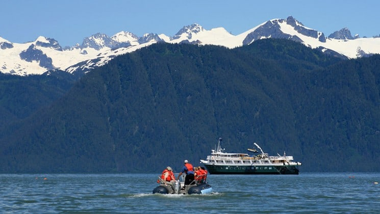 Skiff of passengers going back to their small ship cruise in Alaska with snowy mountains behind