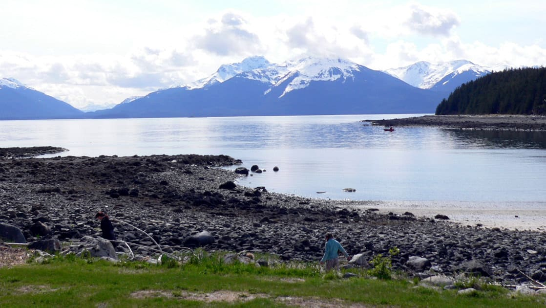 Two people hiking along the shoreline from their small ship cruise in Alaska