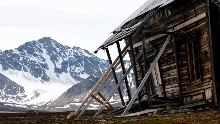 abandoned dilapidated house with arctic mountains behind in spitsbergen
