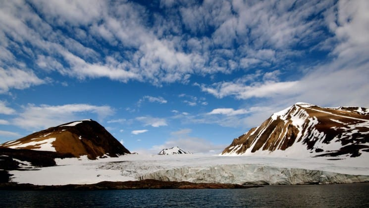 polar landscape under blue sky with wispy clouds on arctic cruise