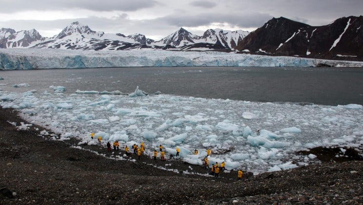 group exploring ice chunks near coast on introduction to spitsbergen: fjords, glaciers & wildlife of svalbard arctic cruise