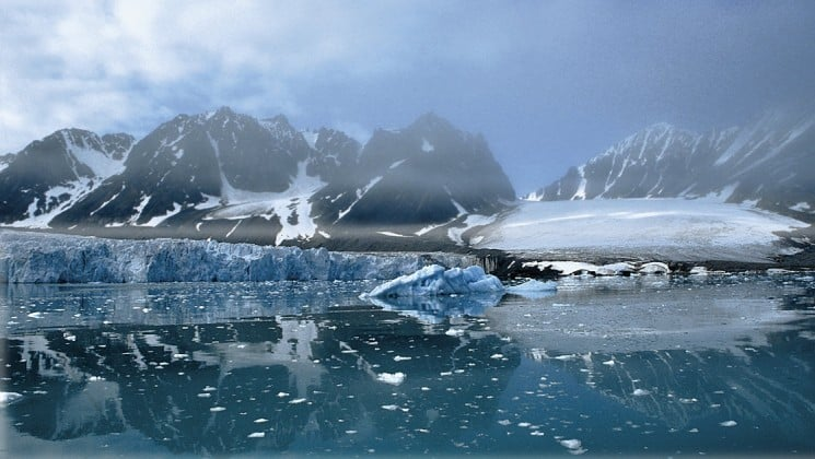 calm waters and fog in reflective arctic landscape of spitsbergen