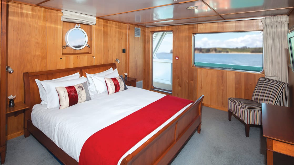 Island Passage Runaway suite with queen bed, seating, desk, porthole and large picture window.