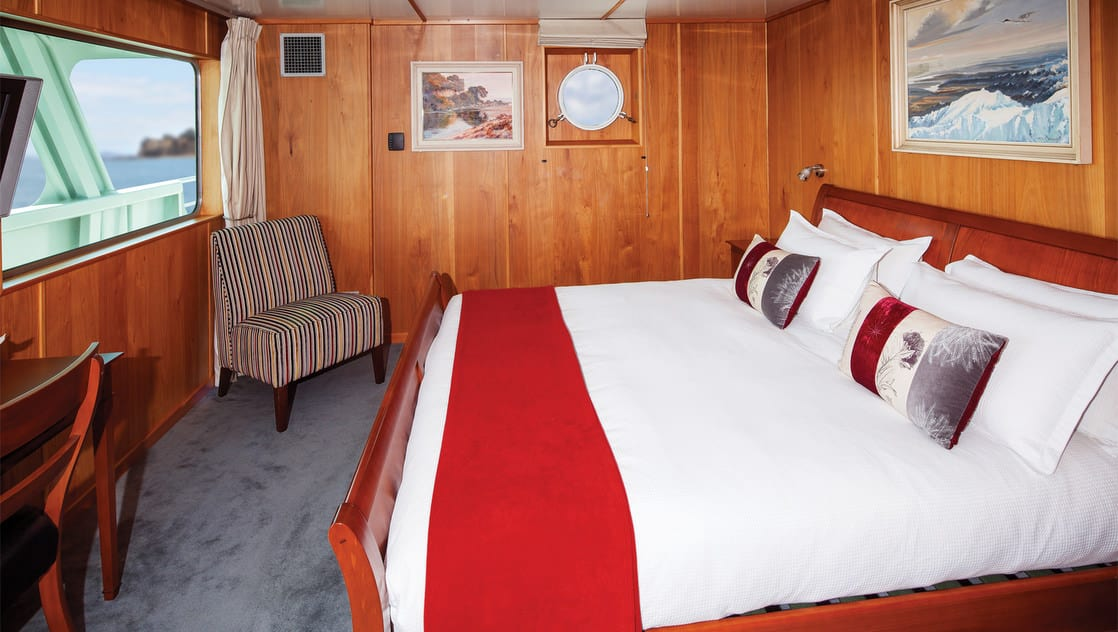 Island Passage Bridge suite with double bed, desk, seating area, large window and porthole.