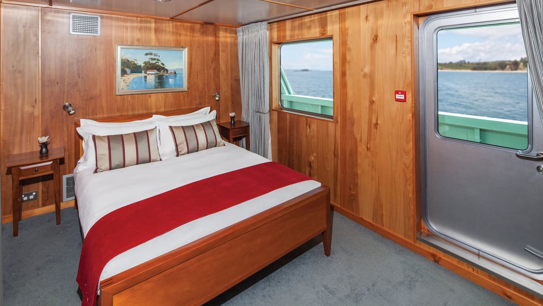 Island Passage Hideaway suite with queen bed, nightstands, reading lights ans 2 large windows.