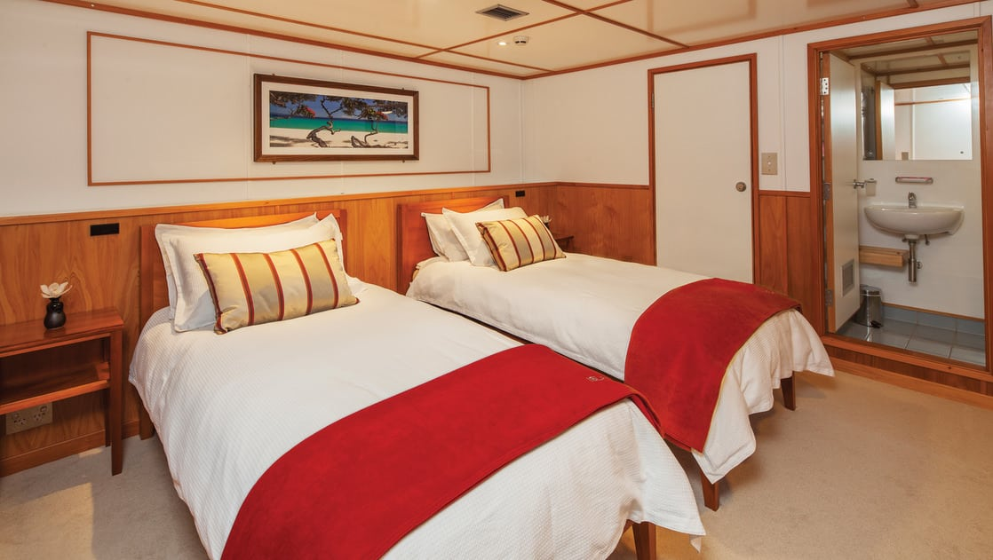 Island Passage Castaway Cabin with twin beds, nightstand and bathroom.