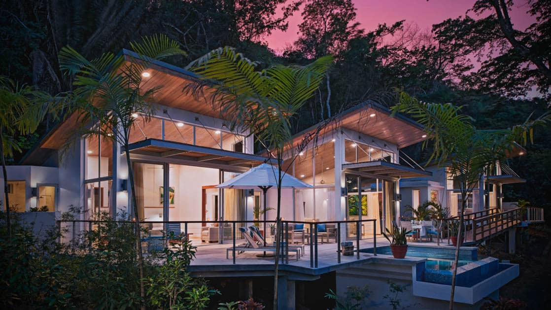 Exterior of Chaa Creek Jungle Lodge at sunset, with large indoor and outdoor living spaces surrounded by lush jungle foliage in Belize