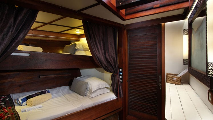 Standard twin stateroom aboard Katharina sailing ship, with twin bunk beds in rich mahogany.