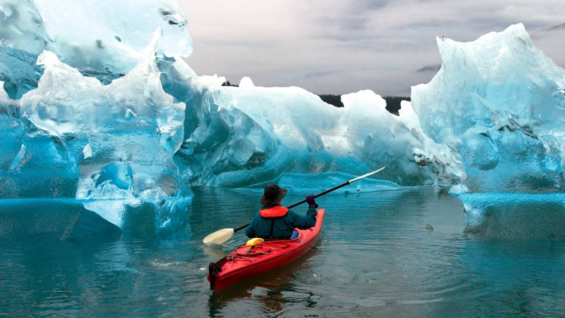 Kayaker paddling through a uniquely sculpted ice berg in tracy arm fjord, Alaska