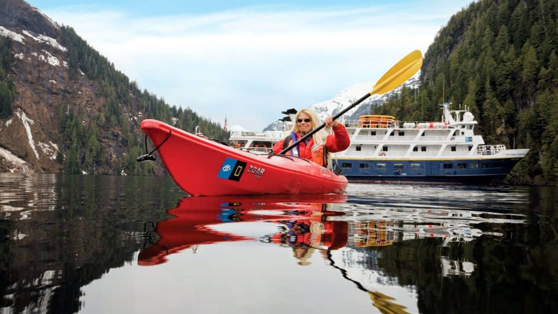 The Lindblad Expeditions ships cruising in Southeast Alaska with a kayaker paddling in front