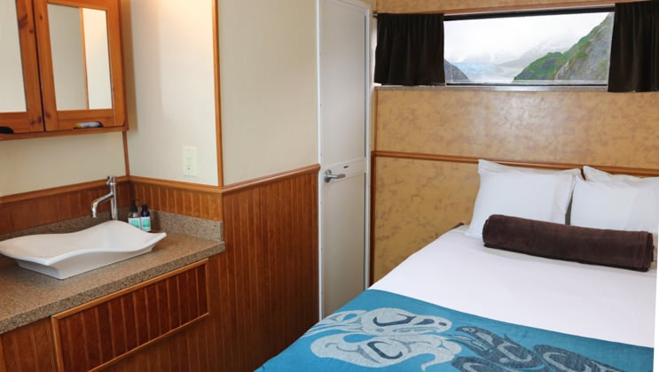 Cabin with queen bed, small window, sink and mirror, with wood accents, on the Kruzof Explorer Alaska small ship.