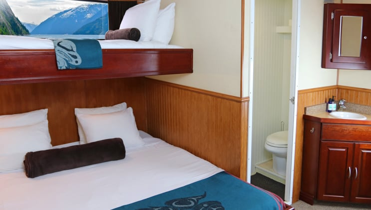 Queen bed with single berth above it, small window, sink, mirror and shoilet, on the Kruzof Explorer Alaska small ship.