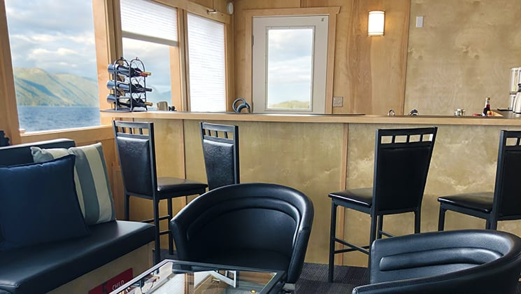 Light-wood bar, view windows & black leather couch & chairs, on the Kruzof Explorer Alaska small ship.